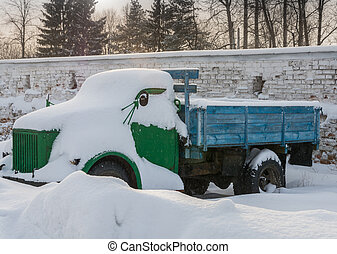 Old truck covered with snow. - Blue-green old truck covered...