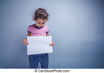 girl child 6 years of European appearance holds a blank slate, l