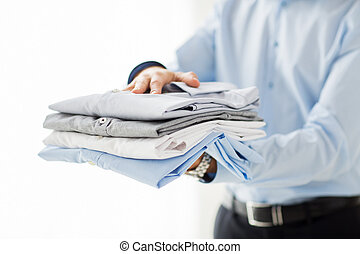 close up of businessman holding folded shirts - business,...