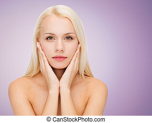 beautiful young woman touching her face - beauty, people and...