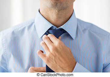 close up of man in shirt adjusting tie on neck - people,...