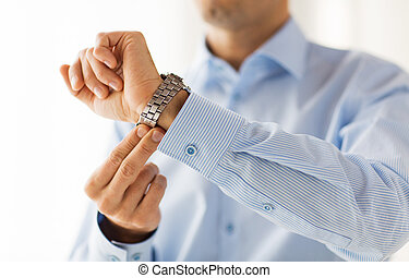 close up of man in shirt fastening wristwatch - people,...