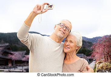 senior couple with camera over asian village - age, tourism,...