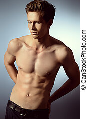 brawny man - Handsome shirtless male model posing at studio....