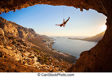 Silhouette of a rock climber falling of a cliff while lead...