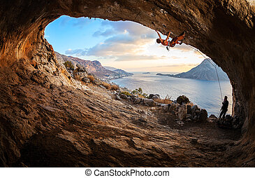 Young woman lead climbing in cave with beautiful view in...