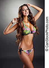 Happy pretty model posing in colorful bikini, on gray...