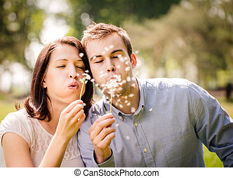 Couple blowing dandelions - Young happy couple blowing...