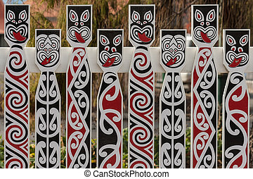 fence with traditional Maori faces - close up of fence with...