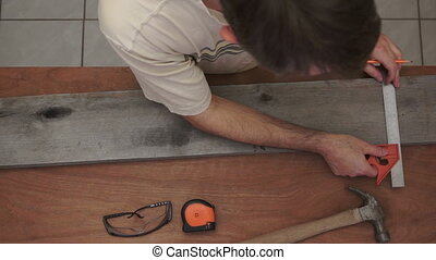 Carpenter Marking Wood Overhead - Overhead shot of a male...