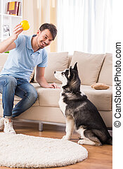 Man with dog - Happy man is playing with his dog at home