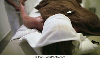 Massage therapist working at beauty spa - Tilt shot of a...