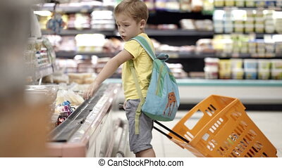 Boy putting products into shopping cart - Boy with backpack...