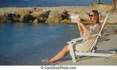Woman with pad making photos of sea sitting in deck chair on beach