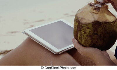 Woman using touch pad and having coconut drink - Close-up...