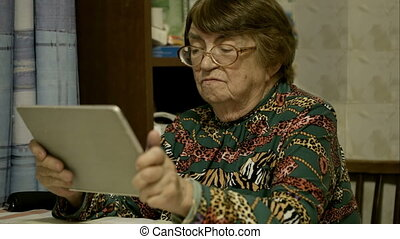 Senior woman using touch pad and talking - Side view of...