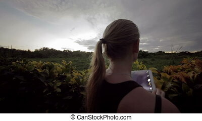 Woman outdoor using tablet PC to make photos of nature scenes