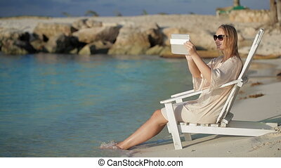Woman with pad making photos of sea sitting in the deck chair on beach