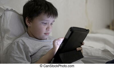 Teenager boy using tablet computer lying in bed