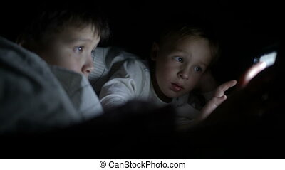 Two little boys try to watch the film at night using the tablet