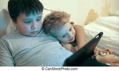Two brothers with pad lying in bed. Entertainment with tablet PC