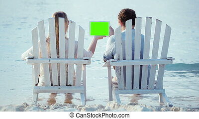 Woman and man sitting on the beach looking at pad with green...