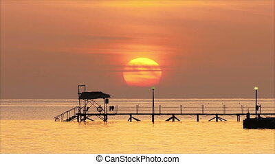 beautiful sunrise over pier in sea - telephoto lens,...