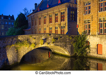 Ancient bridge at Dijver Canal in Bruges at night Belgium -...