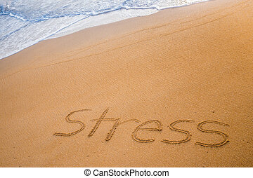 The word STRESS written in the sand - The word STRESS...
