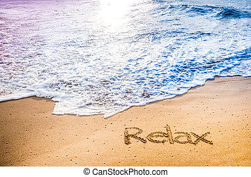 The word RELAX written into the sand on a tropical sandy...
