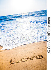 The word LOVE written in the sand - The word LOVE written...