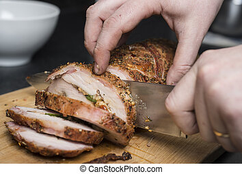 Slicing pork fillet - Slicing filled pork fillet on wooden...