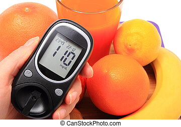 Hand with glucometer, fresh natural fruits, glass of juice -...