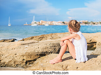 Sad little girl sitting on the beach Place for text