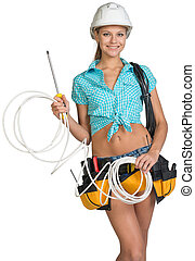 Woman in hard hat and tool belt holding coil of cable -...
