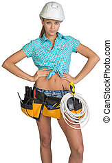 Woman in hard hat and tool belt posing - Woman wearing hard...
