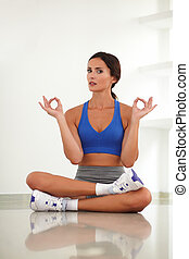 Pretty adult woman exercising in yoga class