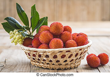Basket with ripe arbutus unedo fruits, leaves and floers on...
