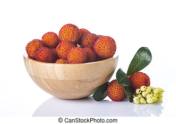 Wooden bowl with arbutus unedo fruits isolated on a white...
