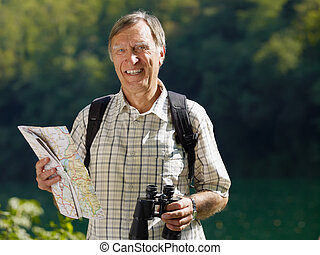 senior hiker holding map and binoculars and looking at...