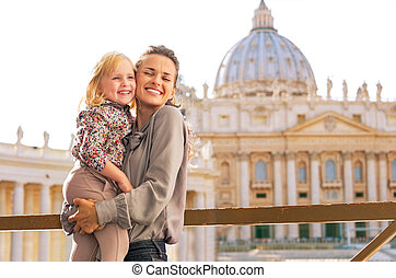 Portrait of happy mother and baby girl hugging on piazza san...