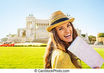 Portrait of smiling young woman with map on piazza venezia...