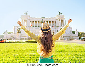 Young woman on piazza venezia in rome, italy rejoicing. rear...