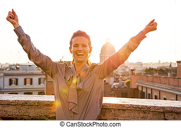 Happy young woman rejoicing on street overlooking rooftops...