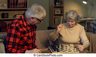 Strategic Thinking - Senior couple playing chess, man...