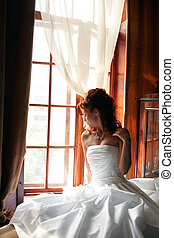 Young bride sat by window - Young adult bride wearing white...