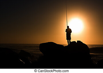 Lone fisherman on rock - Lone fisherman standing on rock in...