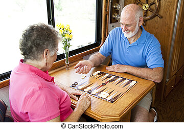 RV Seniors Playing Board Game - Senior couple on vacation...