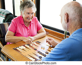 RV Seniors Play Backgammon - Senior couple enjoys a game of...