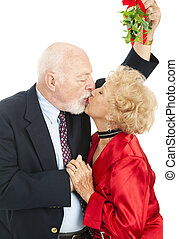 Seniors Under the Mistletoe - Senior couple kissing under...
